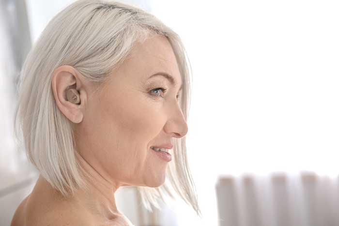 Woman with Hearing aid in ear