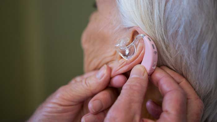 Person is adjusting hearing aid